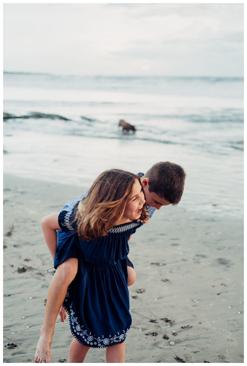 Sister giving her younger brother a piggy back ride on the beach in Playa Avellanas Costa Rica. Photographed by Kristen M. Brown, Samba to the Sea Photography.