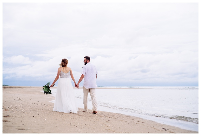 Bride and groom holding hands walking on the beach in Tamarindo Costa Rica. Bride is wearing a Beautiful Adrienna Papell wedding dress. Photographed by Kristen M. Brown, Samba to the Sea Photography.