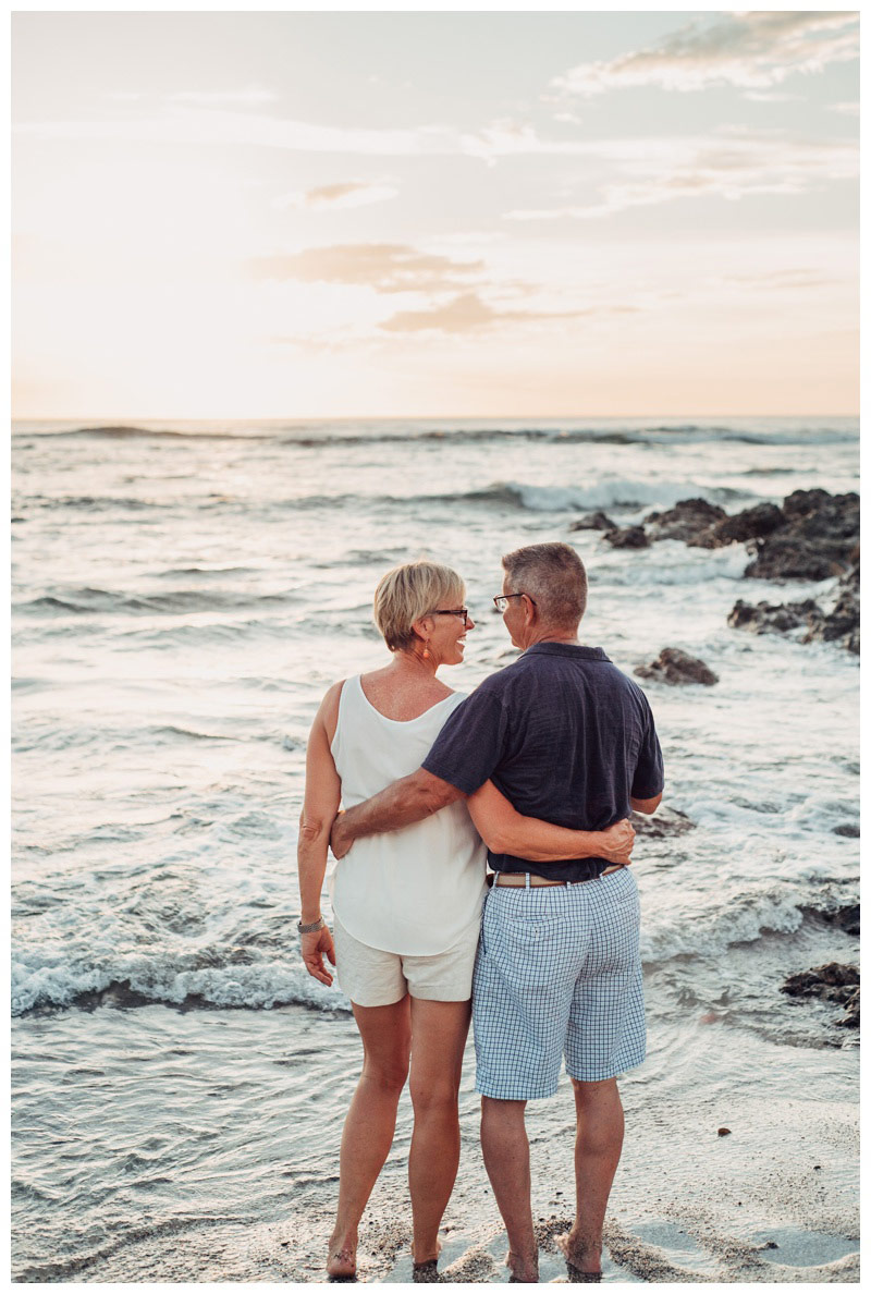 Husband and wife embracing on the beach watching sunset in Playa Langosta Costa Rica. Playa Langosta Costa Rica family photography. Photographed by Kristen M. Brown, Samba to the Sea Photography.