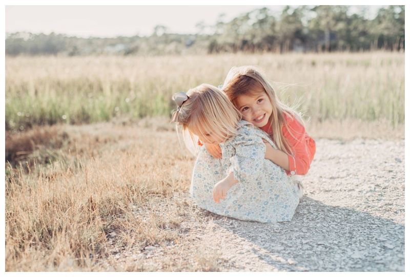 Girl hugging her little sister during Fall family pictures in Savannah Georgia at The Landings on Skidaway Island. Photographed by Kristen M. Brown, Samba to the Sea Photography.