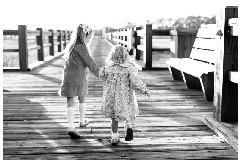 Sisters holding hands walking at Delegal Marina on Skidaway Island in Savannah GA. Fall family pictures in Savannah Georgia at The Landings on Skidaway Island. Photographed by Kristen M. Brown, Samba to the Sea Photography.