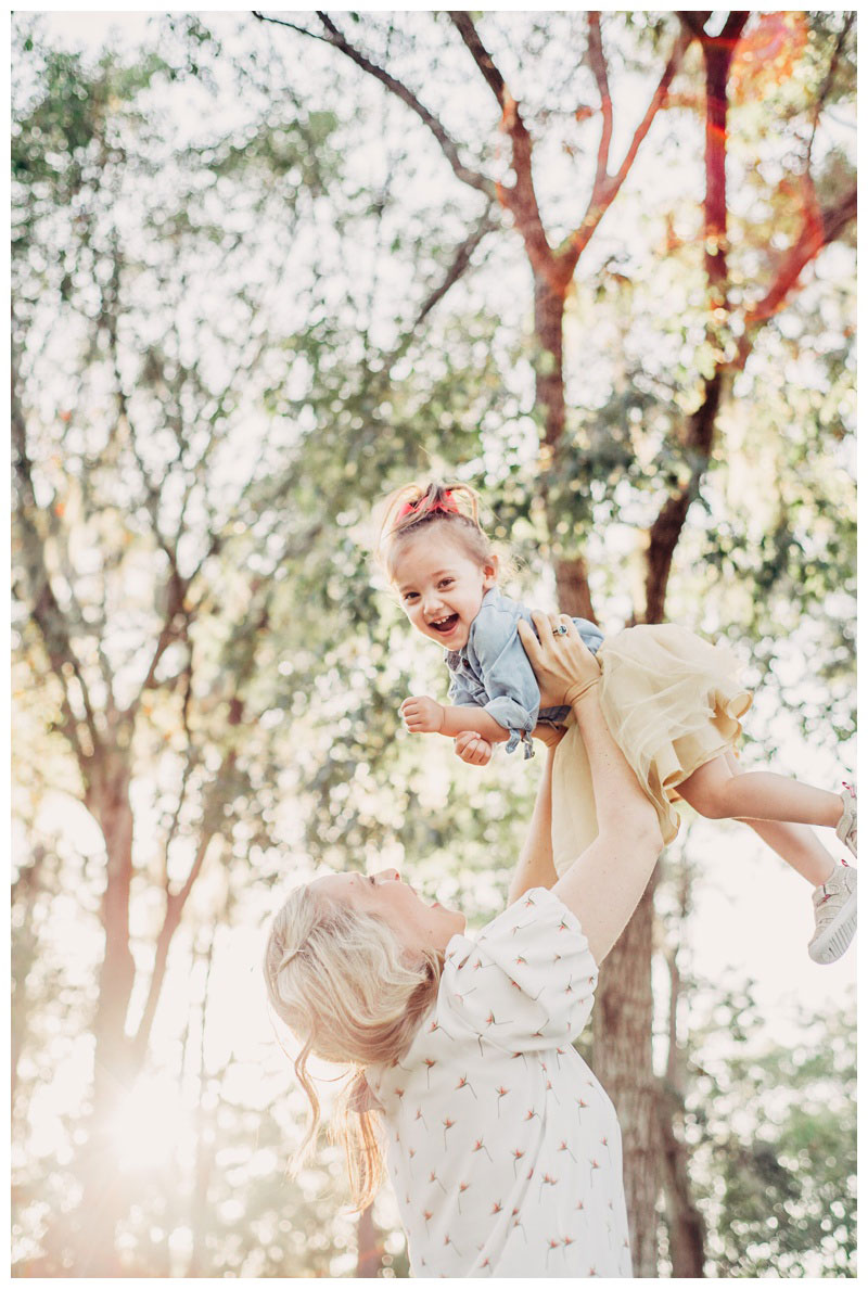 Mother throwing her daughter in the air during family photos at The Landings in Savannah. Photographed by Kristen M. Brown, Samba to the Sea Photography.