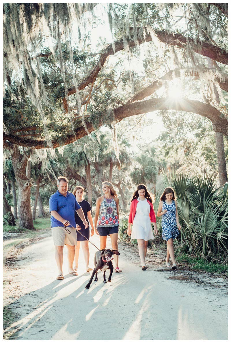 Family walking their dog on a beautiful path during golden hour in Savannah Georgia. Beautiful glowing Spanish moss. Photographed by Kristen M. Brown, Samba to the Sea Photography.