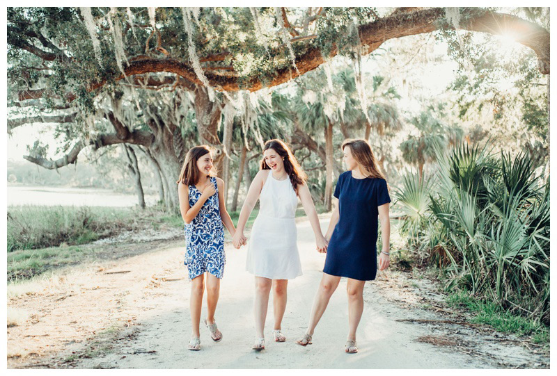 Sisters walking on a beautiful path during golden hour in Savannah Georgia with glowing Spanish moss. Photographed by Kristen M. Brown, Samba to the Sea Photography.