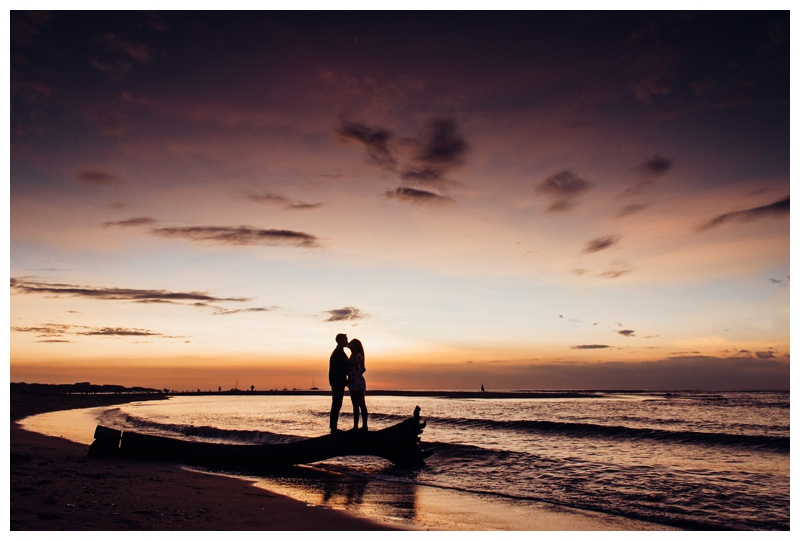 Couple kissing on a piece of driftwood on the beach during a gorgeous sunset in Costa Rica. Photographed by Kristen M. Brown, Samba to the Sea Photography.