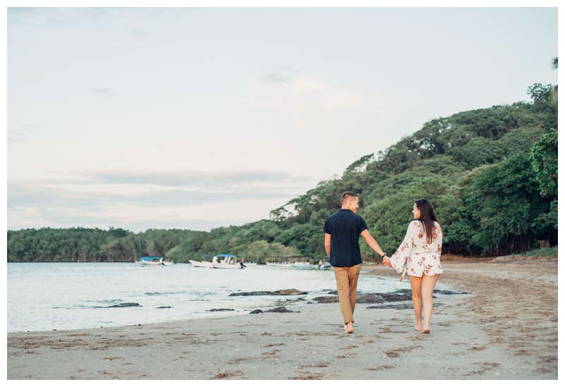 Couple holding hands walking on the beach in Tamarindo Costa Rica. Photographed by Kristen M. Brown, Samba to the Sea Photography.