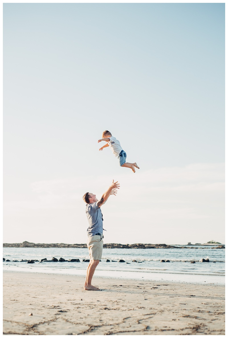 Father throwing his son in the air during family photos in Tamarindo Costa Rica. Photographed by Kristen M. Brown, Samba to the Sea Photography.