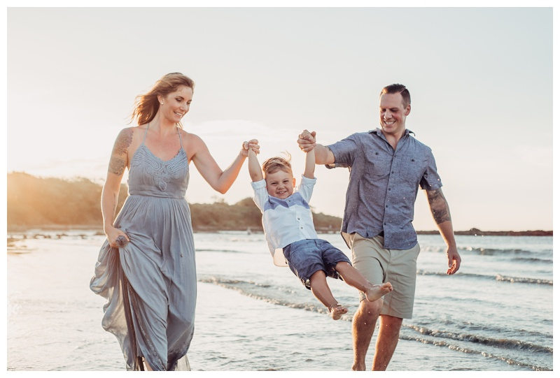 Parents swinging their son on the beach in Costa Rica. Photographed by Kristen M. Brown, Samba to the Sea Photography.