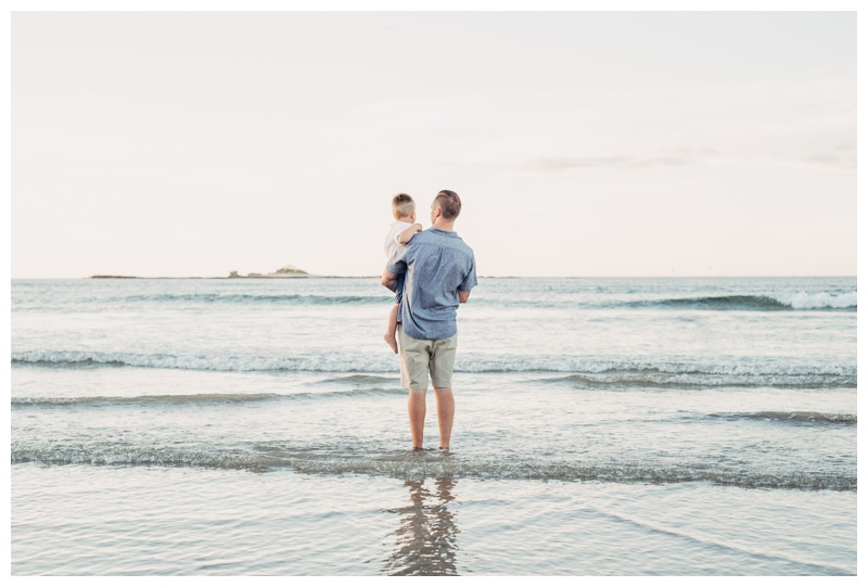 Father holding his son looking at the ocean in Tamarindo Costa Rica. Photographed by Kristen M. Brown, Samba to the Sea Photography.