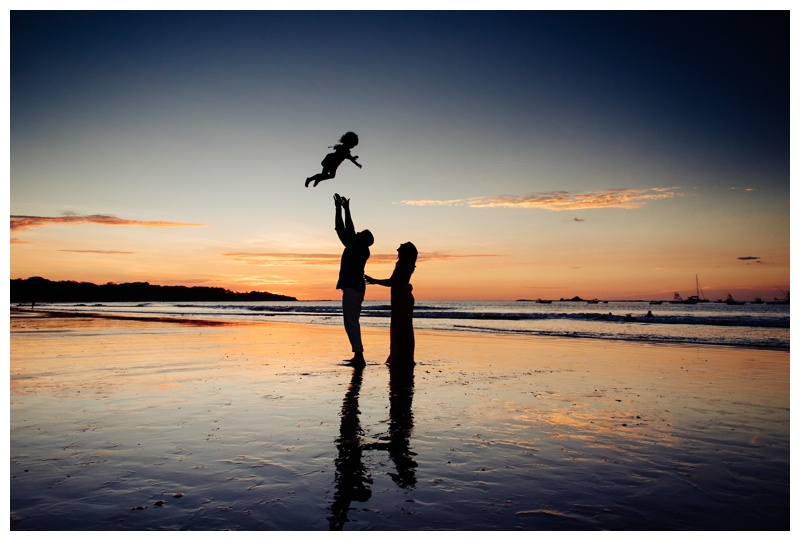 Dad throwing daughter in the air during gorgeous sunset in Costa Rica. Photographed by Kristen M. Brown, Samba to the Sea Photography.
