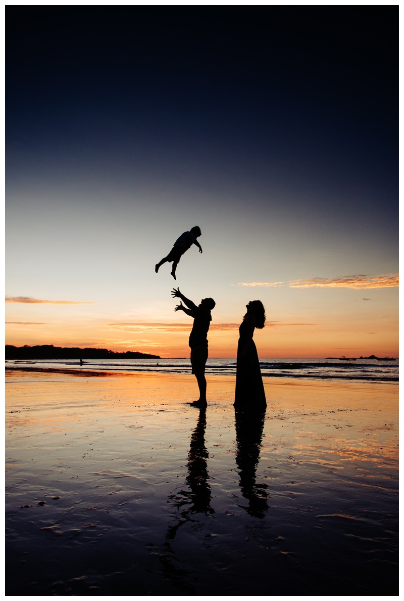 Dad throwing son in the air during gorgeous sunset in Costa Rica. Photographed by Kristen M. Brown, Samba to the Sea Photography.