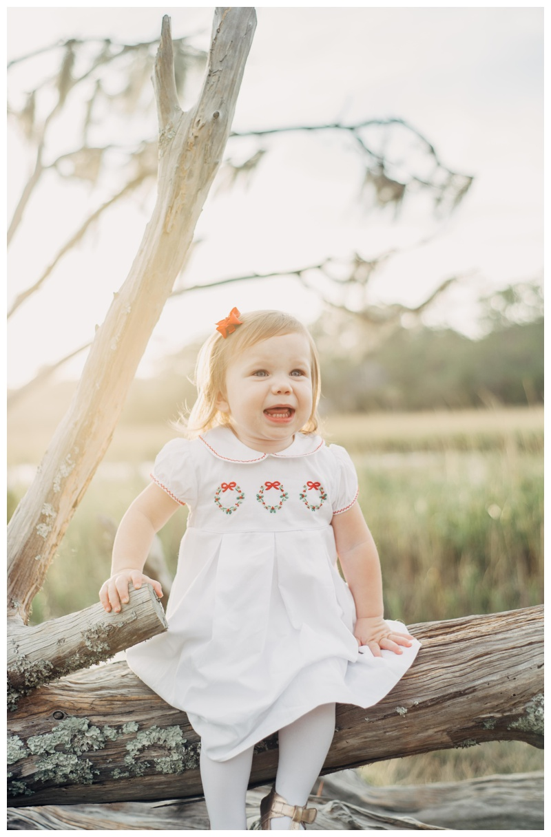 Little girl smiling in her white Christmas dress. Holiday family pictures in Savannah Georgia at The Landings on Skidaway Island. Photographed by Kristen M. Brown, Samba to the Sea Photography.