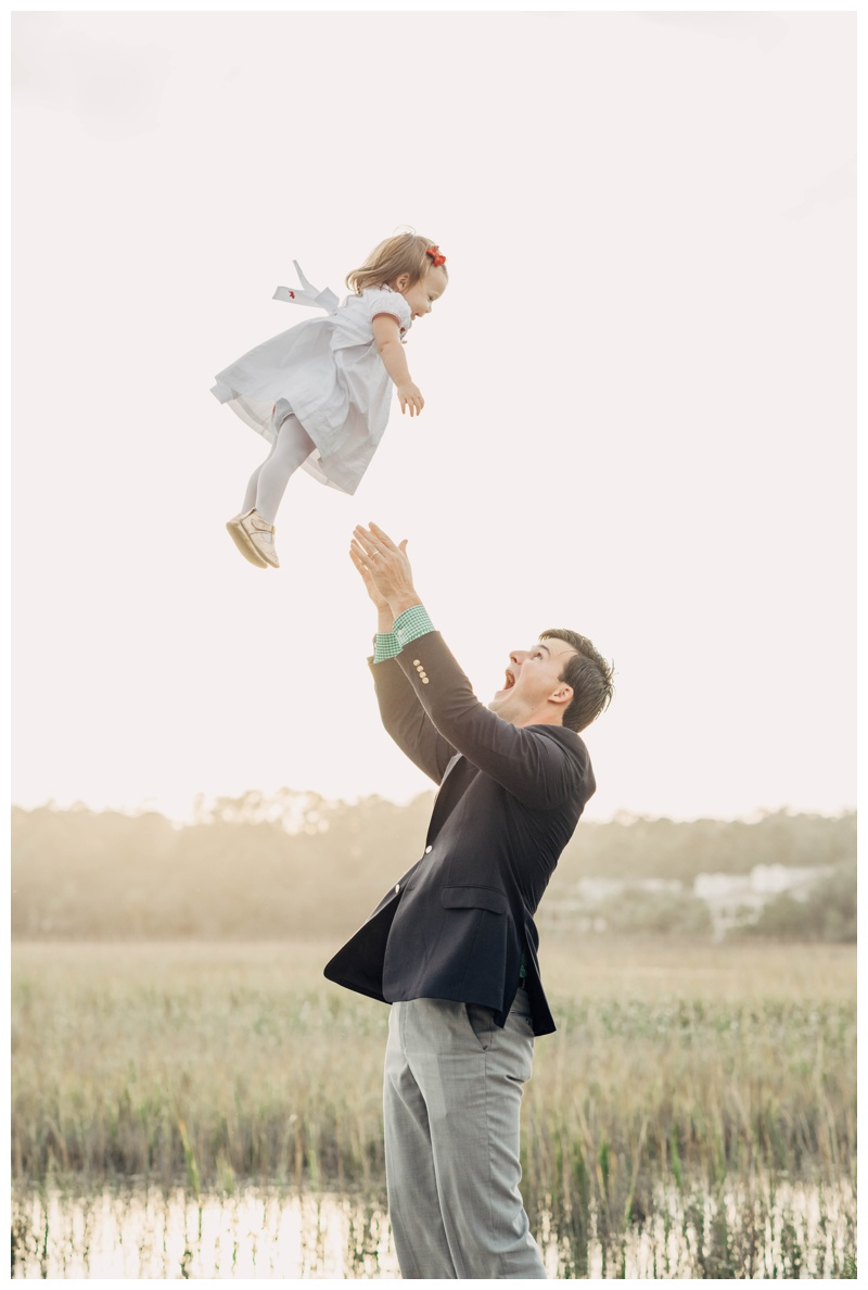 Father throwing his little girl in the air during family photos in Savannah. Holiday family pictures in Savannah Georgia at The Landings on Skidaway Island. Photographed by Kristen M. Brown, Samba to the Sea Photography.