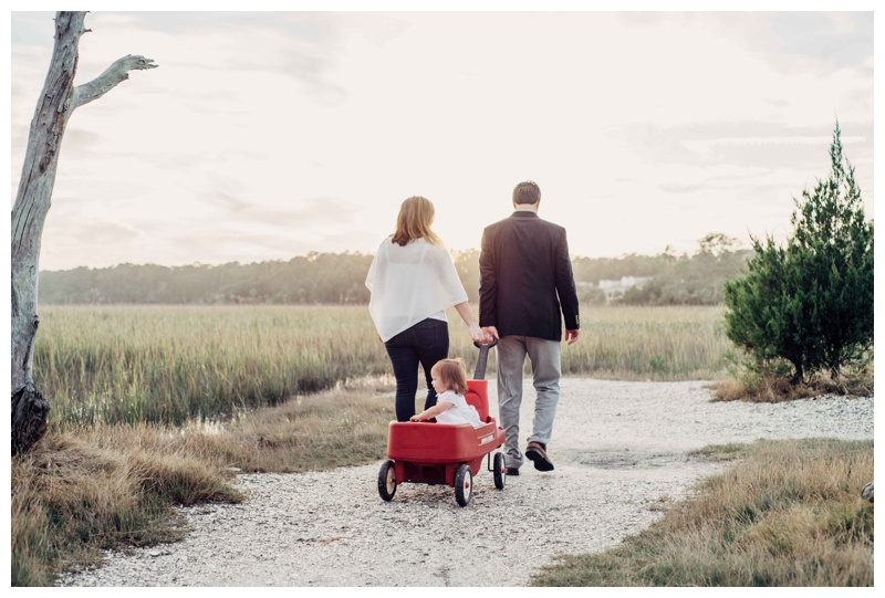 Little girl riding in her little red wagon during family photos in Savannah.