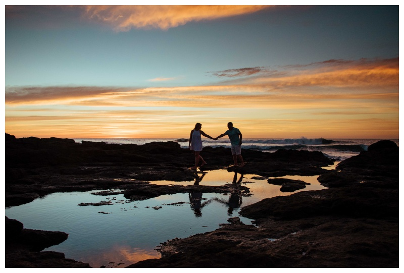 Couple walking on low tide rocks during a beautiful sunset in Costa Rica. Photographed by Kristen M. Brown, Samba to the Sea Photography.