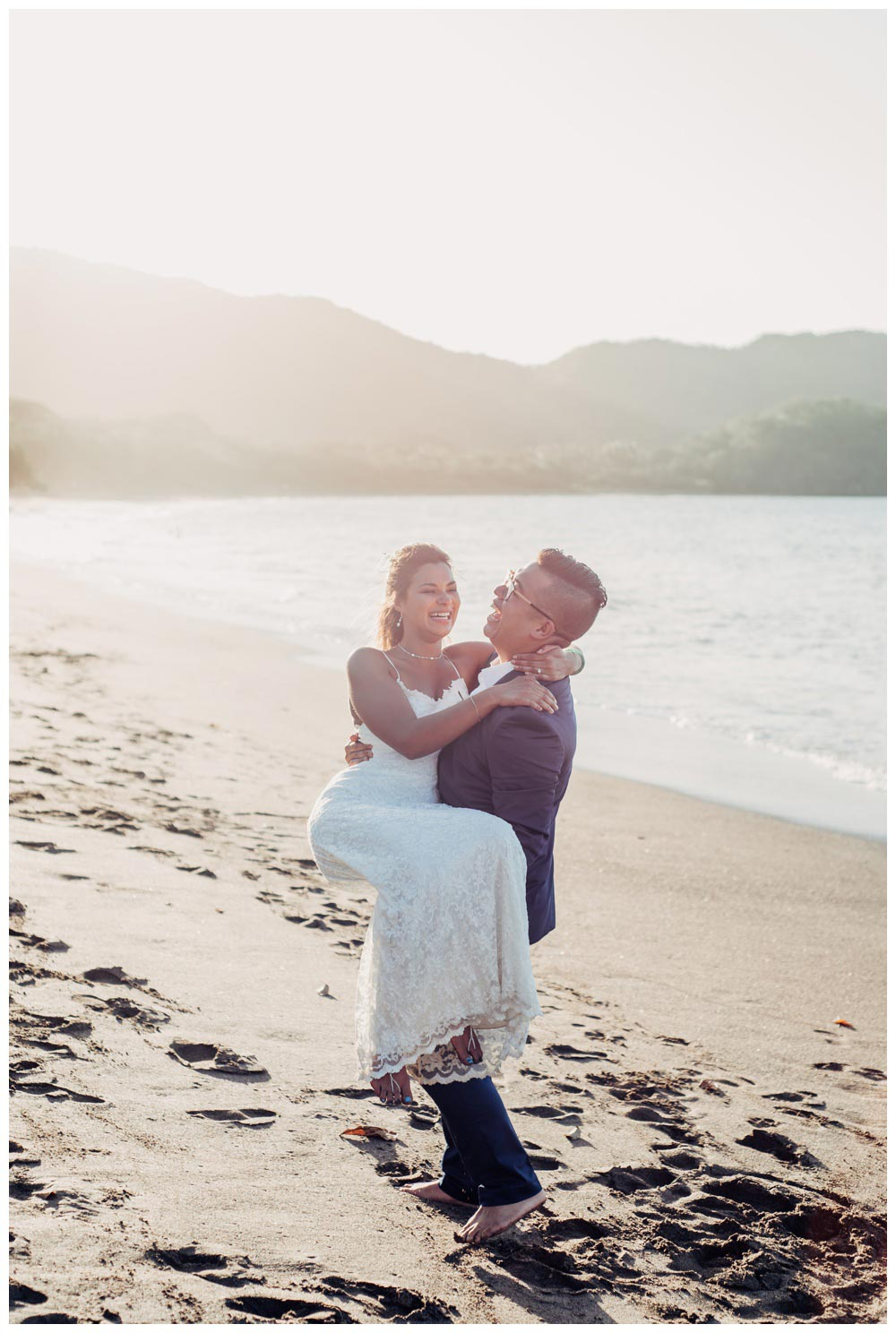 Groom carrying his bride on the beach in Costa Rica. Wedding in Guanacaste Costa Rica. Photographed by Kristen M. Brown, Samba to the Sea Photography.