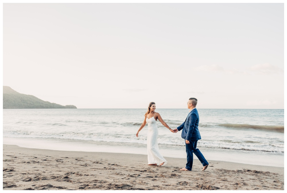 Bride and groom walking on the beach during golden hour in Costa Rica. Wedding in Guanacaste Costa Rica. Photographed by Kristen M. Brown, Samba to the Sea Photography.