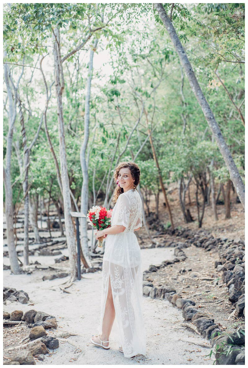 Bride walking on a beach path at the Andaz Papagayo. Magical sailboat elopement in Costa Rica. Photographed by Kristen M. Brown, Samba to the Sea Photography.