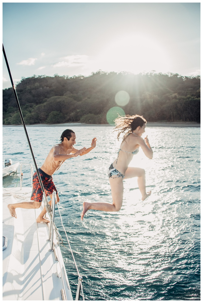 Bride and groom jumping off the sailboat during their magical sailboat elopement in Costa Rica. Photographed by Kristen M. Brown, Samba to the Sea Photography.