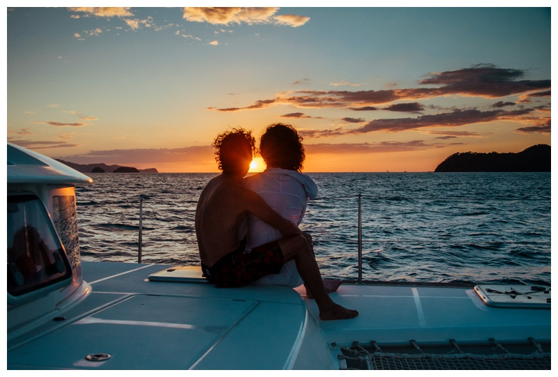 Bride and groom watching sunset from the sailboat during their magical sailboat elopement in Costa Rica. Photographed by Kristen M. Brown, Samba to the Sea Photography.