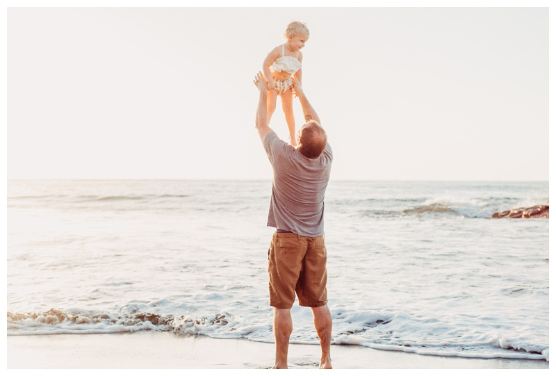 Father throwing his daughter in the air on the beach with his mom in Nosara Costa Rica. Photographed by Kristen M. Brown, Samba to the Sea Photography.
