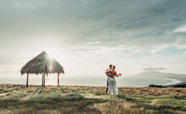 Groom kissing his bride after their elopement in Tamarindo, Costa Rica. Photographed by Kristen M. Brown, Samba to the Sea Photography.