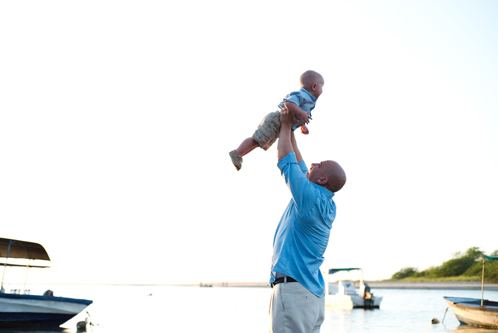 Father throwing his young son in the air on the beach in Tamarindo, Costa Rica. Photographed by Kristen M. Brown, Samba to the Sea Photography.