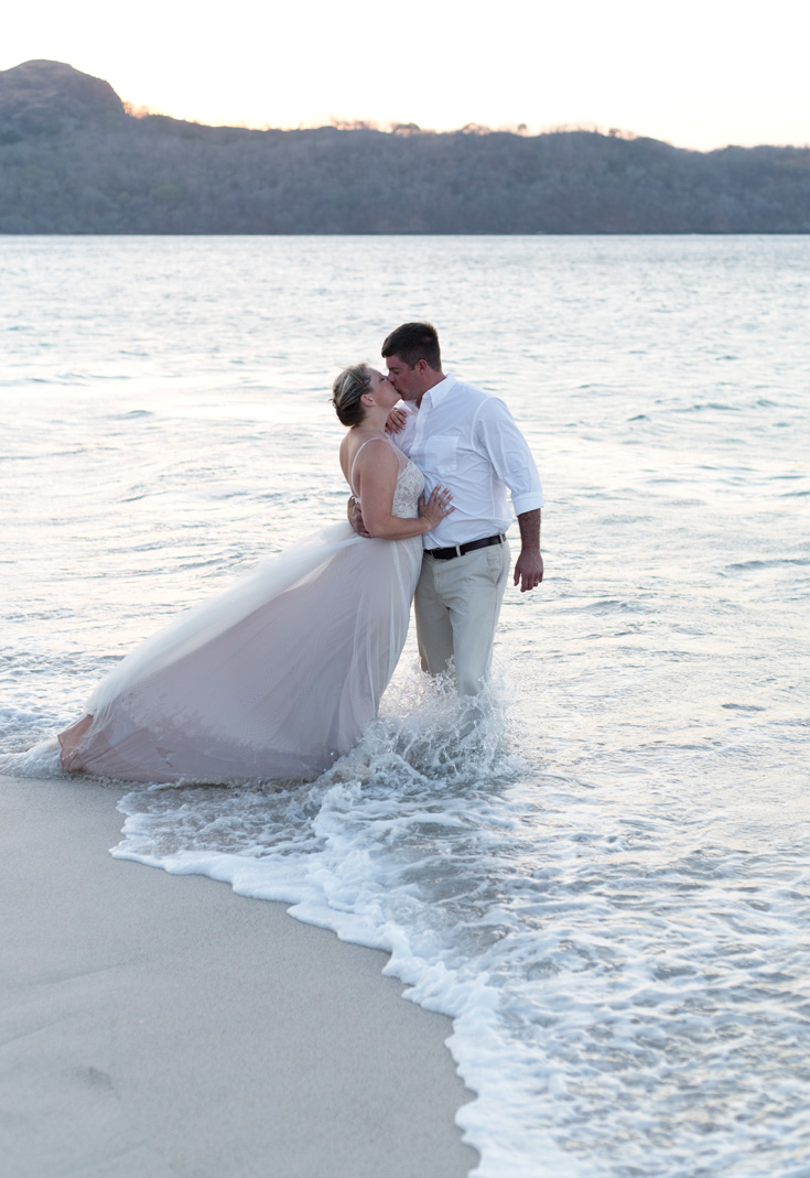 Bride and groom kissing on the shoreline at Playa Conchal, Costa Rica. Photographed by Kristen M. Brown, Samba to the Sea Photography.