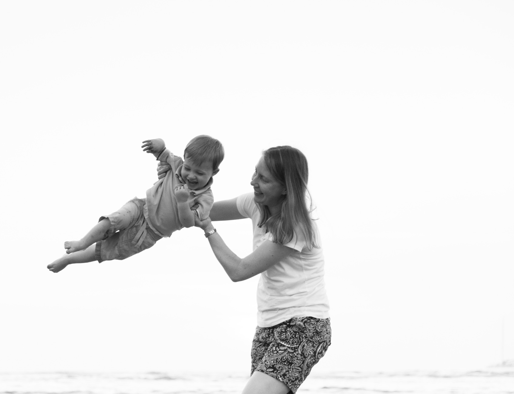 Mom spinning her young son in Tamarindo, Costa Rica. Photographed by Kristen M. Brown, Samba to the Sea Photography.
