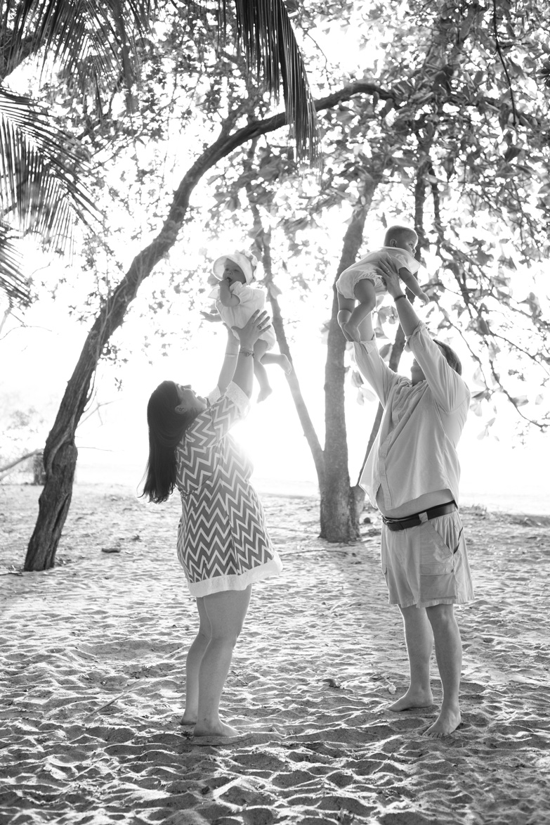 Parents throwing twin babies in the air on the beach in Tamarindo, Costa Rica. Photographed by Kristen M. Brown, Samba to the Sea Photography.