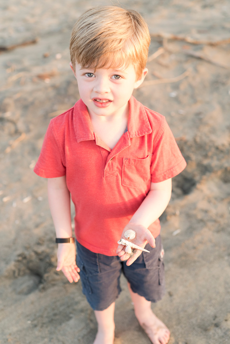 Young boy holding seashells on the beach in Tamarindo, Costa Rica. Photographed by Kristen M. Brown, Samba to the Sea Photography.