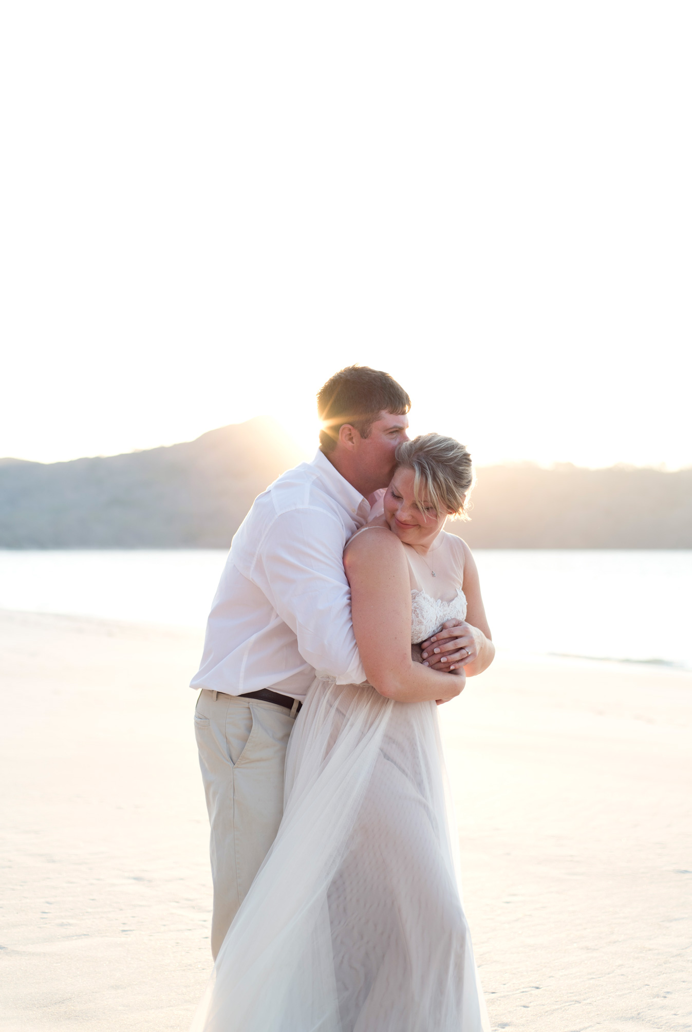 Groom hugging bride on Playa Conchal Wedding. Photographed by Kristen M. Brown, Samba to the Sea Photography.