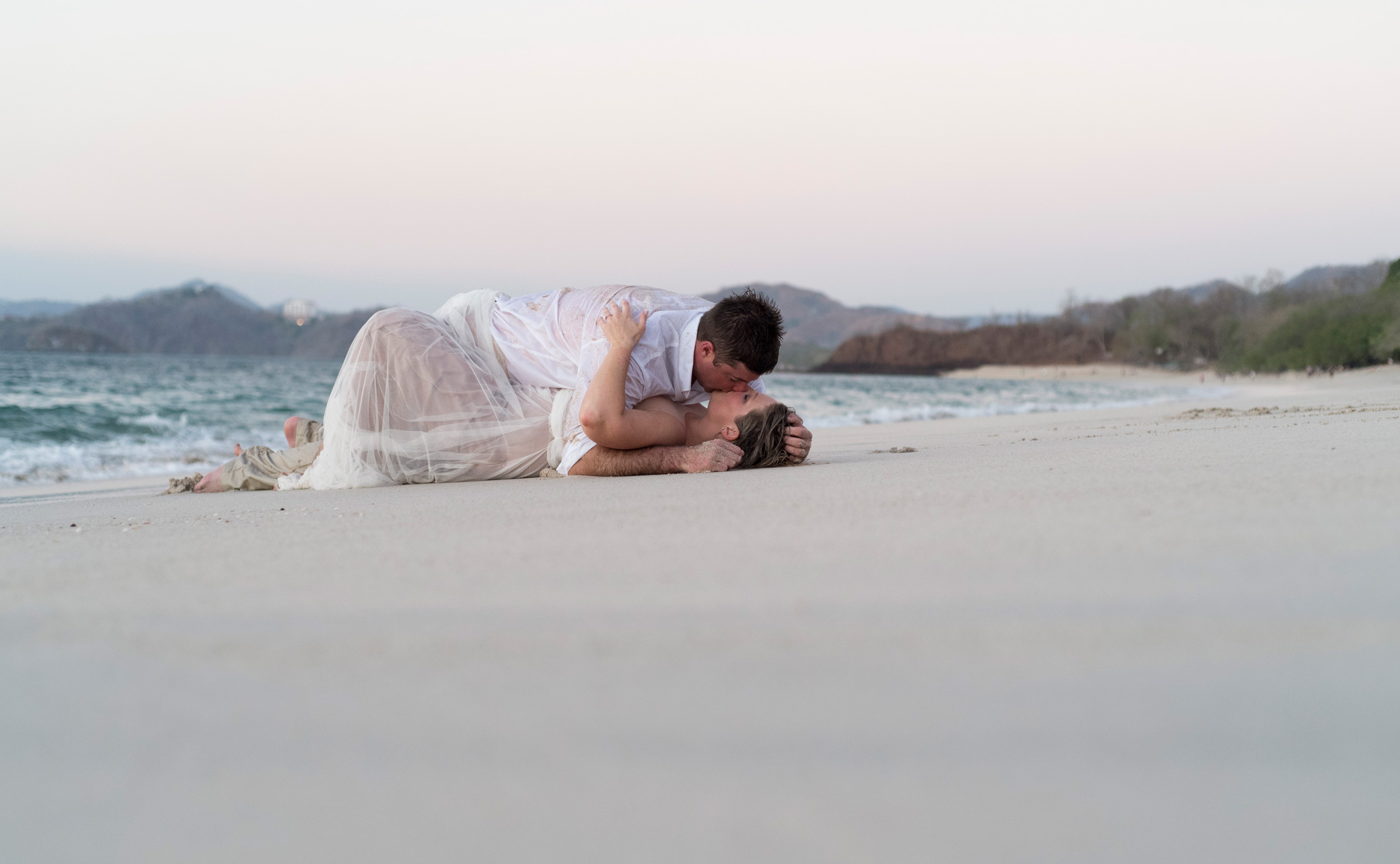 Bride and groom romantically kissing ton the beach at Playa Conchal, Costa Rica. Photographed by Kristen M. Brown, Samba to the Sea Photography.
