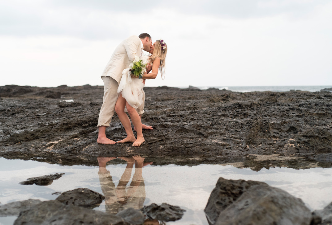 Groom dipping bride after wedding on Playa Langosta, Costa Rica. Photographed by Kristen M. Brown, Samba to the Sea Photography.