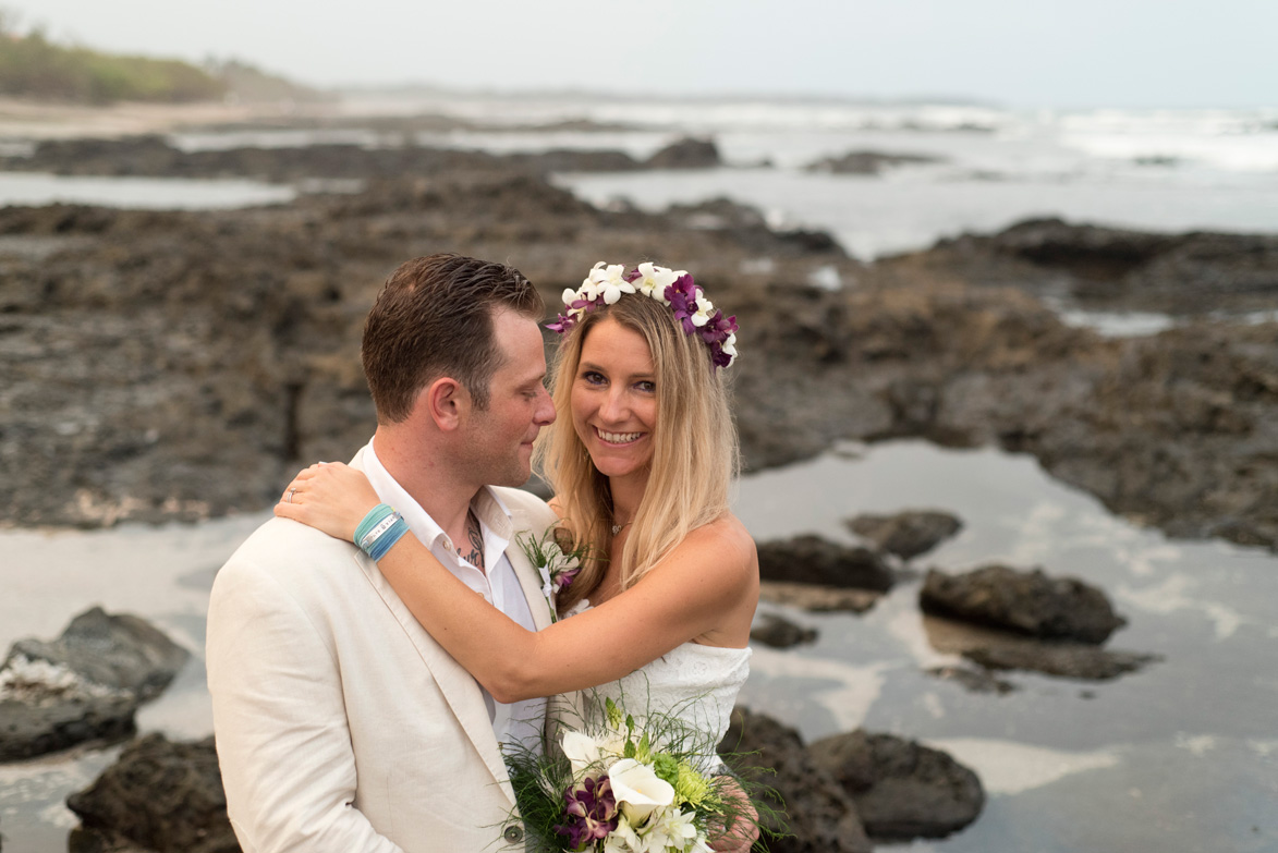 Bride wearing purple and white flower crown and hugging groom after wedding in Playa Langosta, Costa Rica. Photographed by Kristen M. Brown, Samba to the Sea Photography.