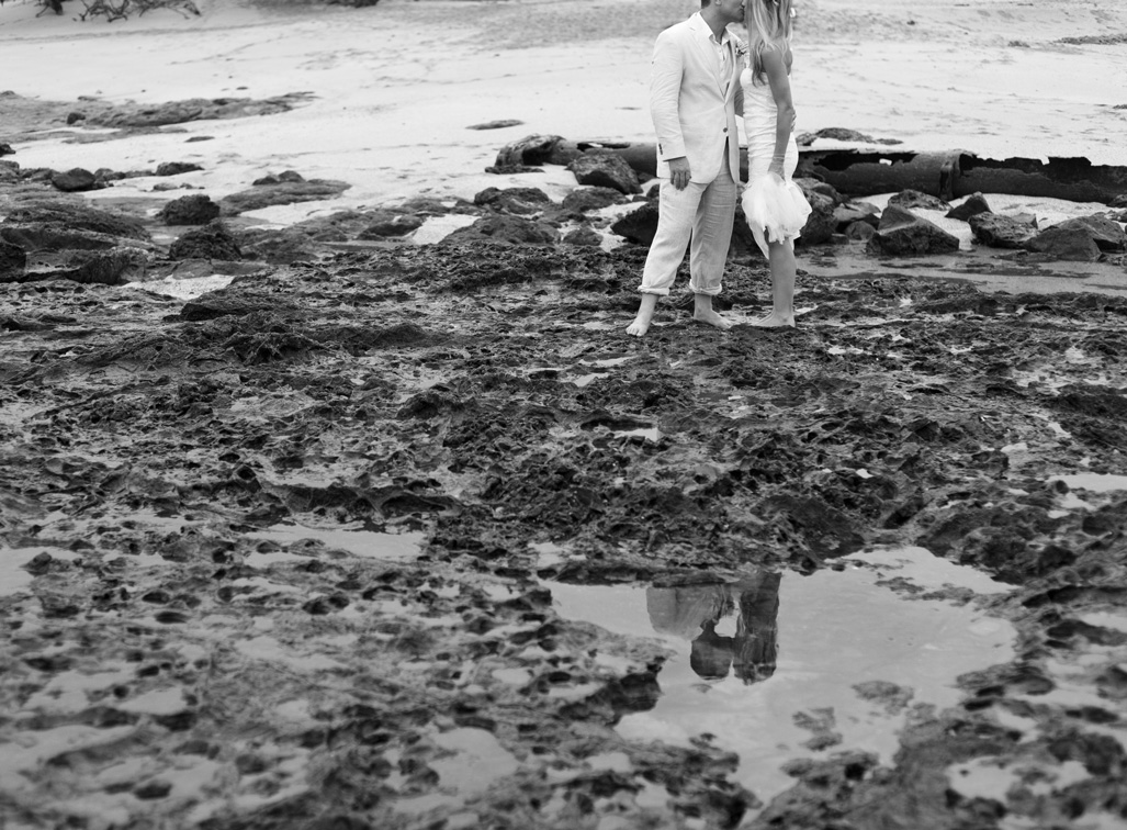 Black and white photo of reflection of bride and groom kissing after wedding at Cala Luna in Playa Langosta, Costa Rica. Photographed by Kristen M. Brown, Samba to the Sea Photography.