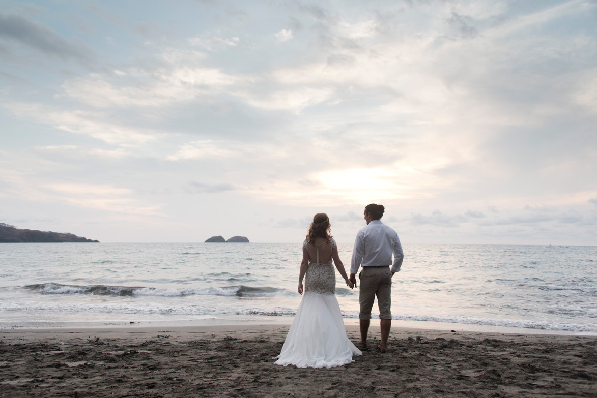Bride and groom holding hands at sunset on the beach at Playa Hermosa, Costa Rica. Bride and groom standing on the low tide rocks at Playa Hermosa, Costa Rica. Photographed by Kristen M. Brown, Samba to the Sea Photography.