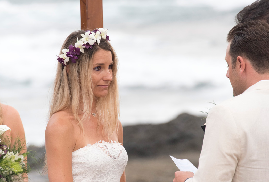 Bride tearing up as groom says his vows at wedding in Playa Langosta, Costa Rica. Photographed by Kristen M. Brown, Samba to the Sea Photography.