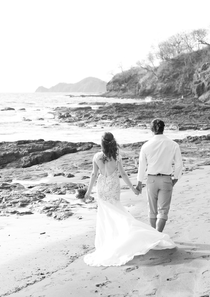 Bride and groom walking on the beach at Playa Hermosa, Costa Rica. Photographed by Kristen M. Brown, Samba to the Sea Photography.