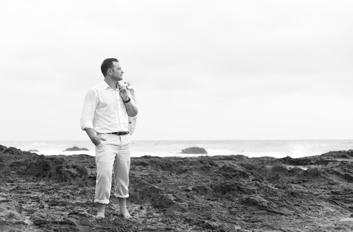 Black and white photo of groom on the low tide rocks in Playa Langosta, Costa Rica. Photographed by Kristen M. Brown, Samba to the Sea Photography.