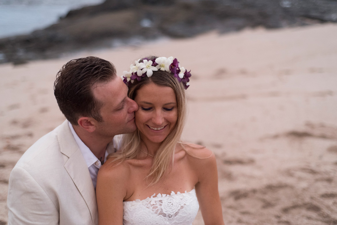 Groom kissing bride on the cheek in Playa Langosta, Costa Rica. Photographed by Kristen M. Brown, Samba to the Sea Photography.