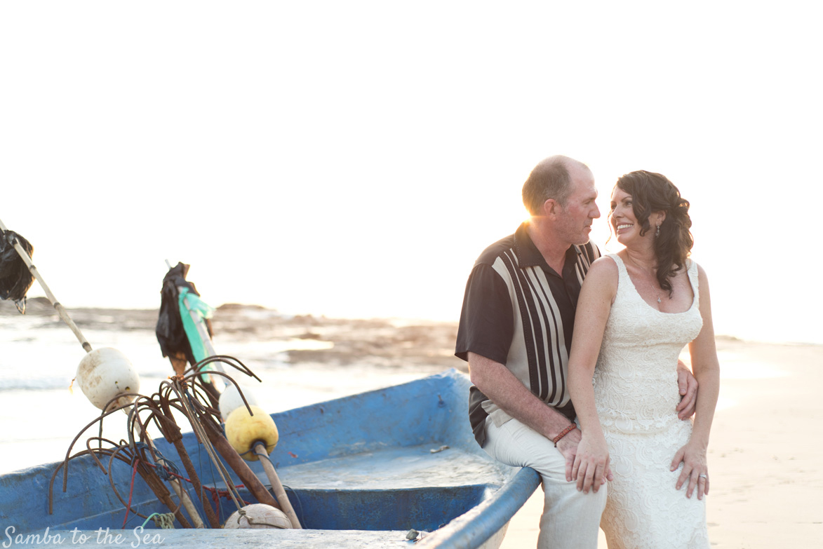 Bride and groom sitting on a panga boat in Nosara, Costa Rica. Photographed by Kristen M. Brown, Samba to the Sea Photography.