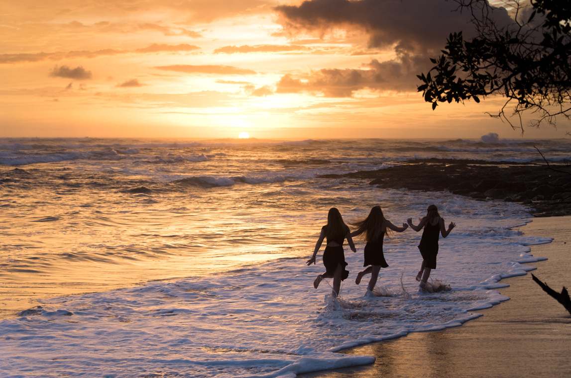 Cousins running on the beach during sunset in Costa Rica. Photographed by Kristen M. Brown, Samba to the Sea Photography.