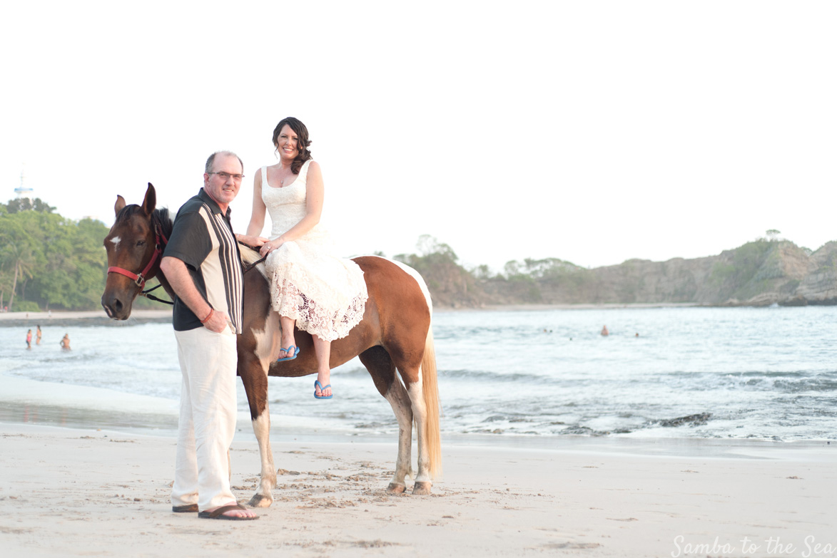 Bride and groom posing with a pinto mare on the beach in Costa Rica. Photographed by Kristen M. Brown, Samba to the Sea Photography.