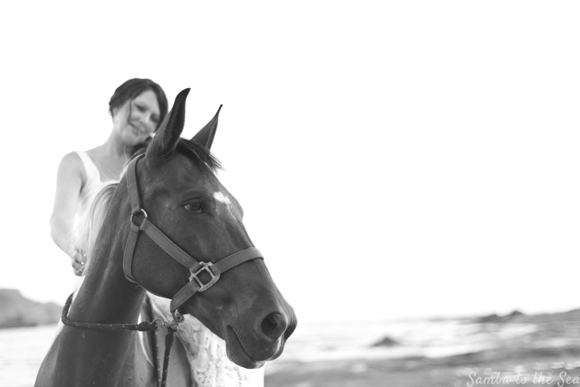 Black and white photo of bride and pinto mare horse. Destination wedding in Nosara, Costa Rica. Photographed by Kristen M. Brown, Samba to the Sea Photography.