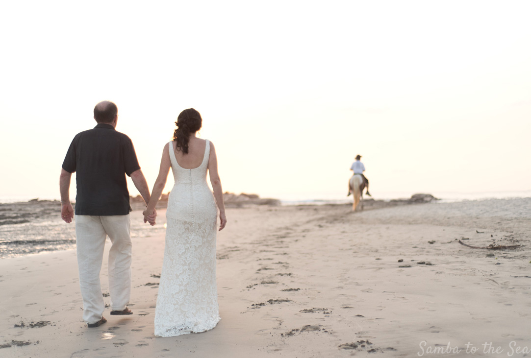 Bride and groom walking on the beach at sunset in Nosara, Costa Rica. Photographed by Kristen M. Brown, Samba to the Sea Photography.