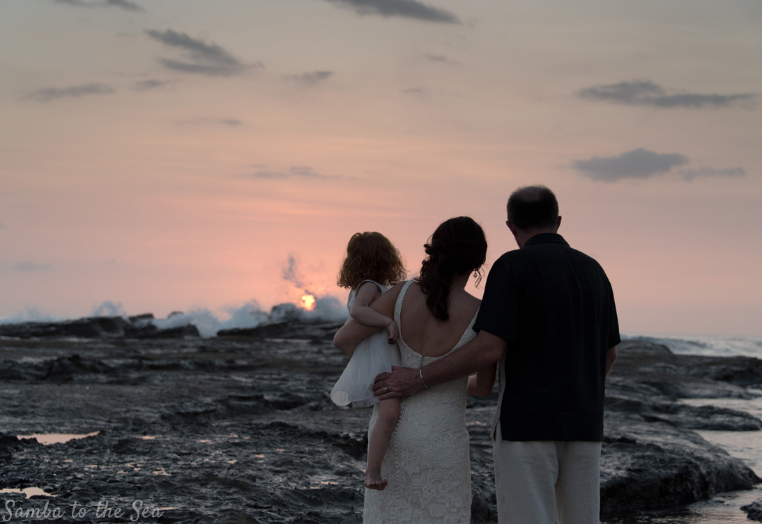 Bride, groom, and daughter watching sunset in Playa Pelada in Nosara, Costa Rica. Photographed by Kristen M. Brown, Samba to the Sea Photography.