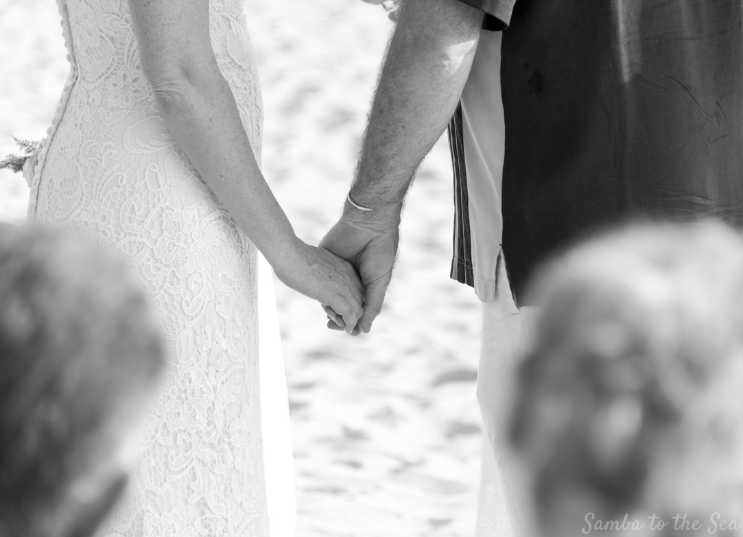 Black and white photo of bride and groom holding hands during wedding ceremony on the beach in Nosara, Costa Rica.