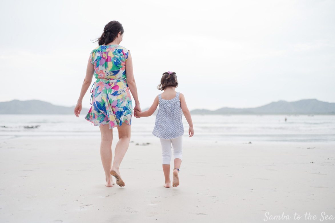 Mother and daughter holding hands on the beach in Tamarindo, Costa Rica. Photographed by Kristen M. Brown, Samba to the Sea Photography.