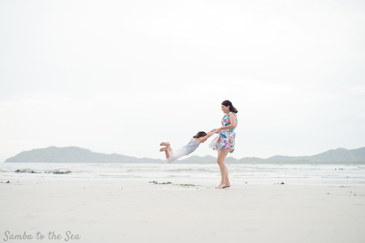Mother swinging her daughter on the beach in Tamarindo, Costa Rica. Photographed by Kristen M. Brown, Samba to the Sea Photography.